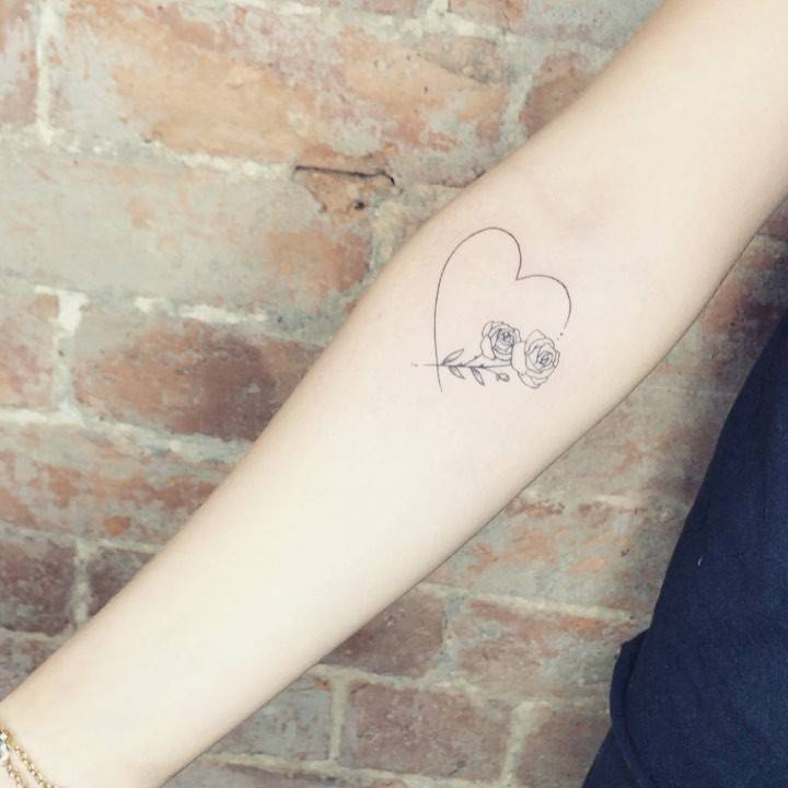 Fine line heart and roses tattoo on the inner forearm.
