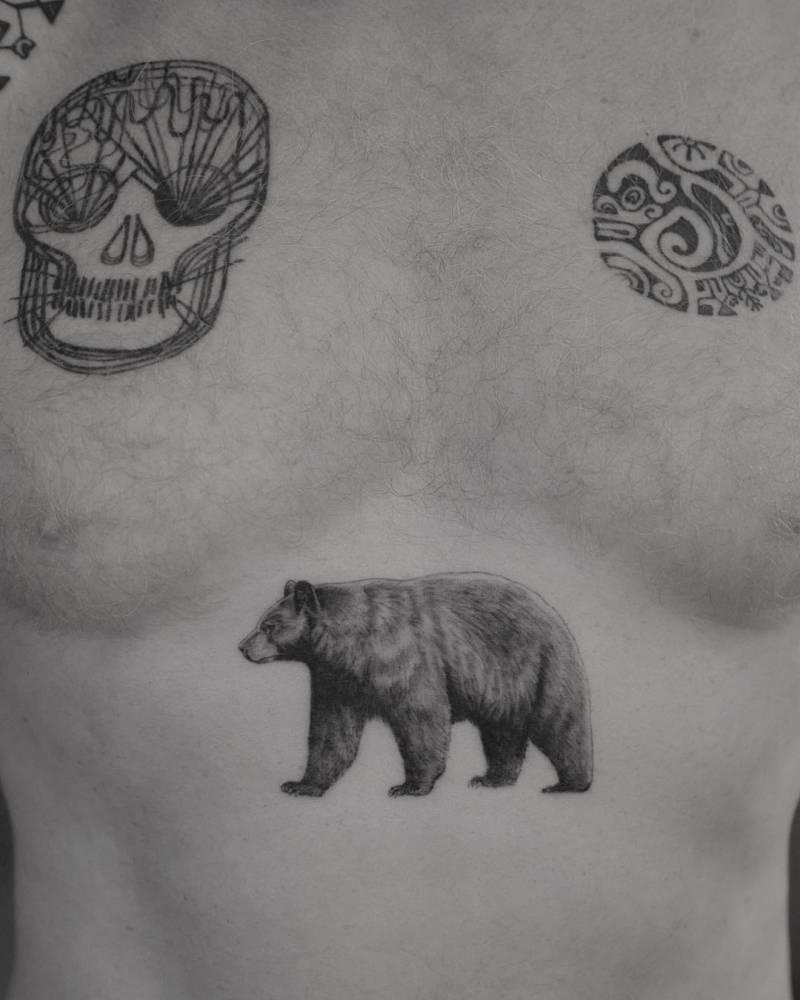 Micro-realistic bear tattoo on Thomas Houseago's stomach.