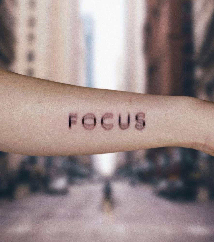 """""""Focus"""" lettering tattoo on the forearm."""
