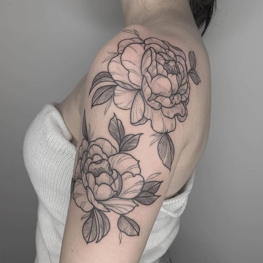Peonies tattoo on the upper arm.