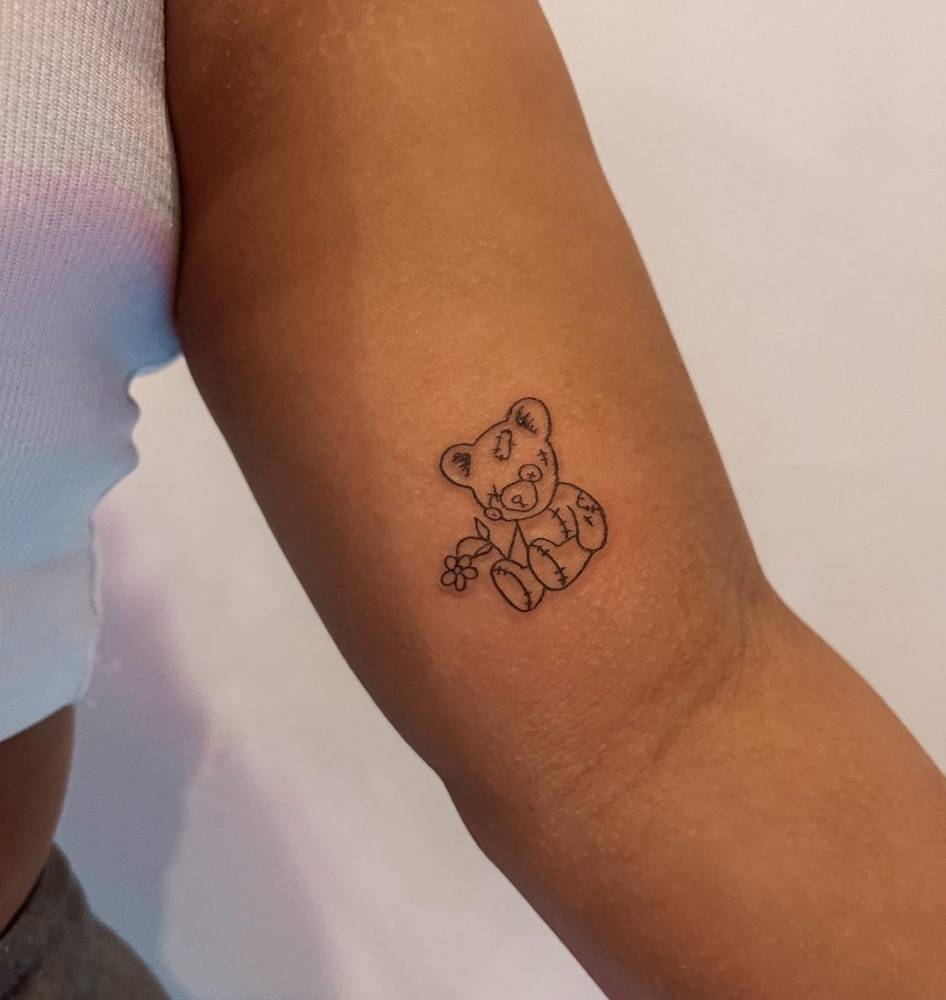 Line art teddy bear tattoo on the inner arm.