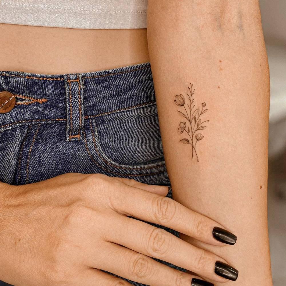 Fine line flower bouquet tattoo on the inner forearm.