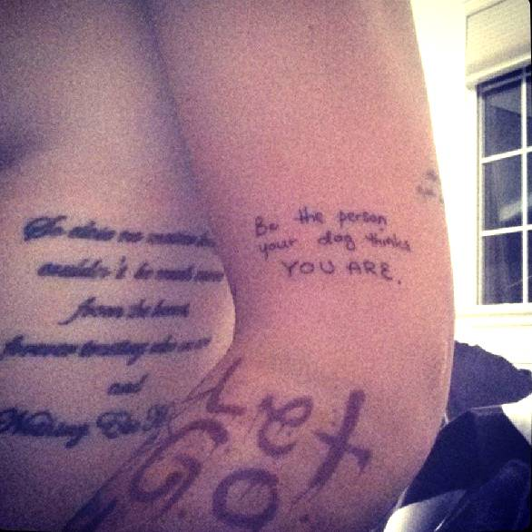 """Ruby Rose's upper arm tattoo """"be the person your dog thinks you are"""", and left side tattoo saying """"So close no matter how far, couldn't be much more from the heart, forever trusting who we are and nothing else matters."""""""
