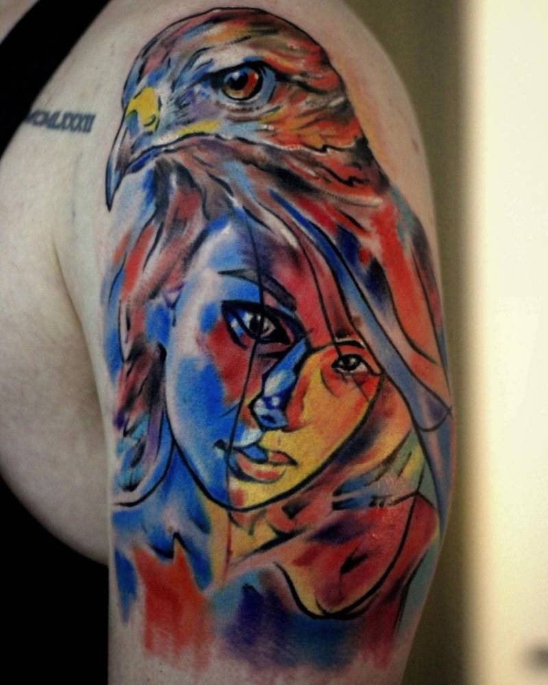 Watercolor woman and eagle tattoo on the upper arm.