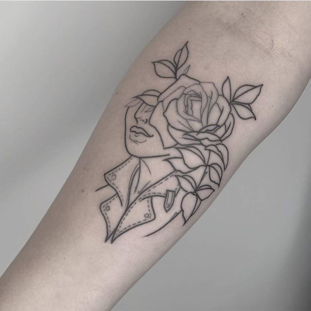 Line art flower head woman tattoo on the inner forearm.