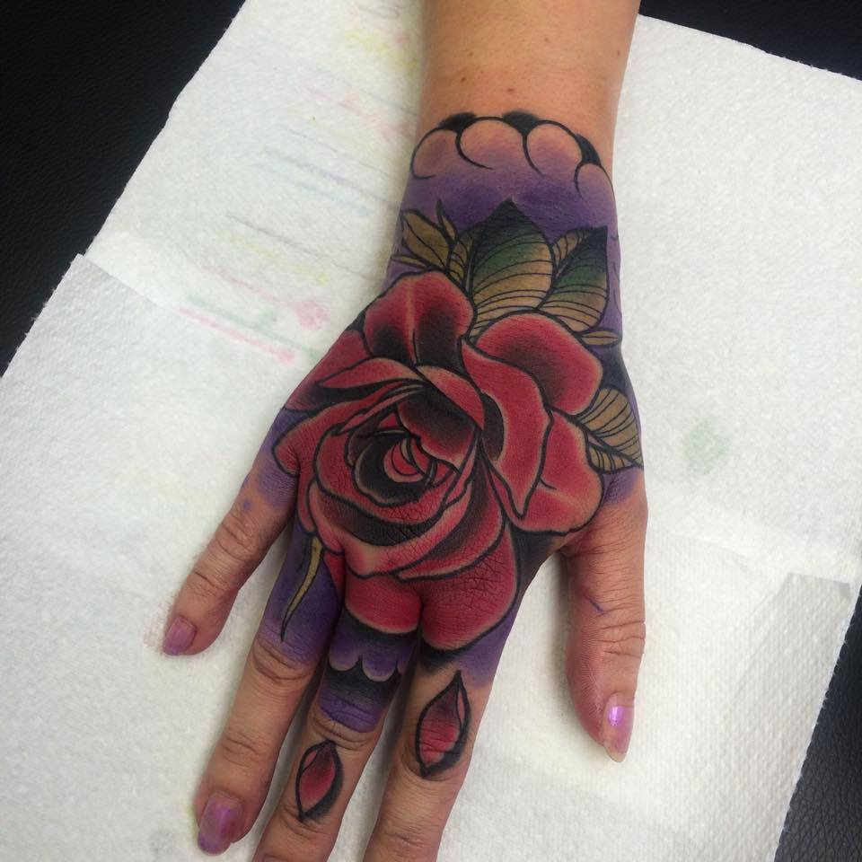 fe266c624 Neotraditional style rose tattoo on the right hand.