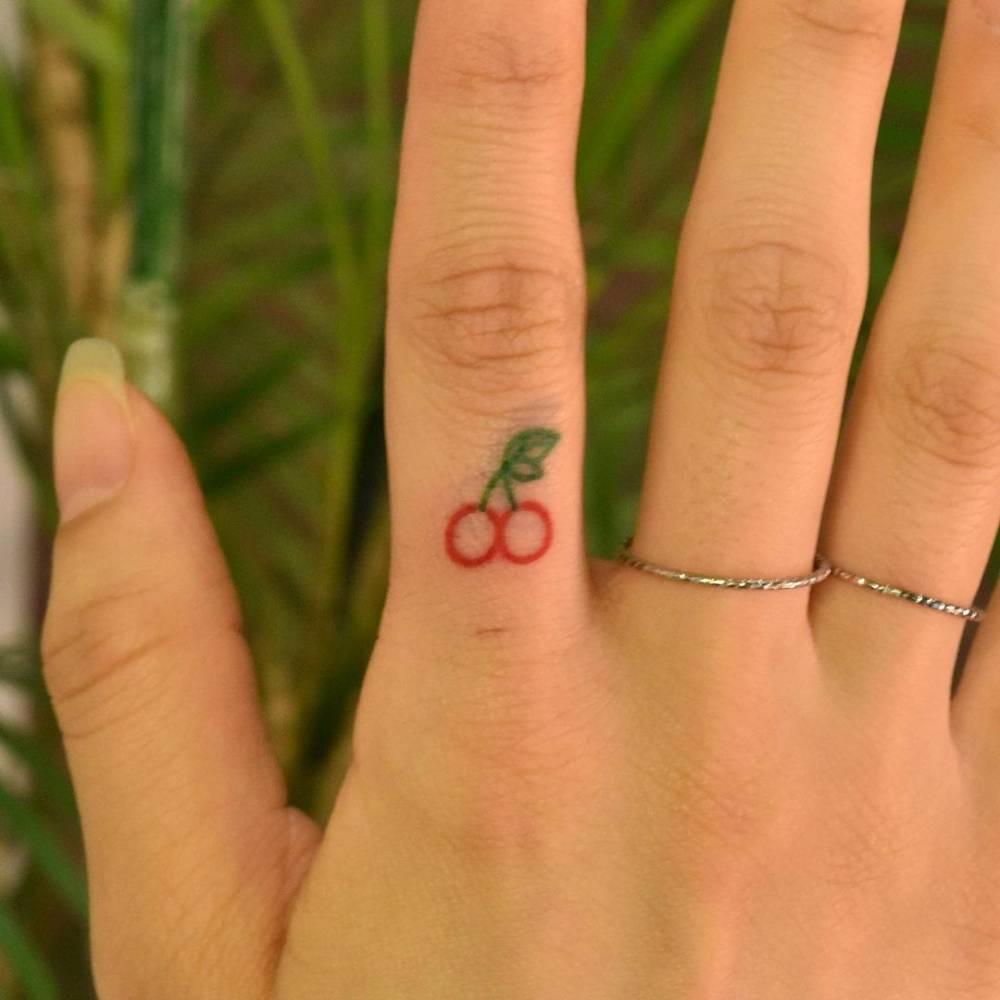 Minimalist cherry tattoo on the finger.