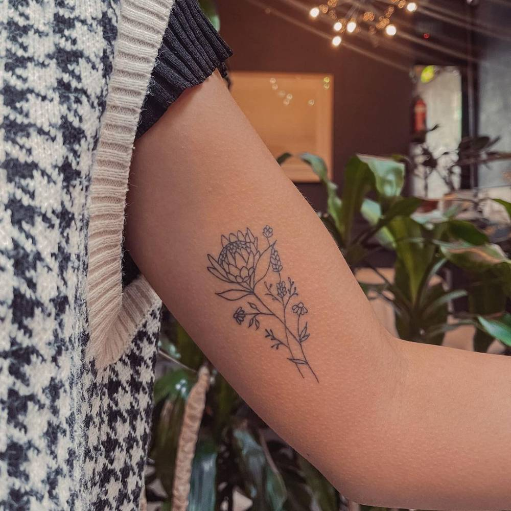 Line art flowers tattoo on the inner arm (healed).