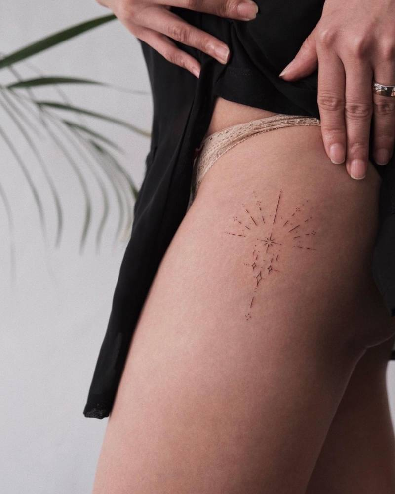 Fine line ornamental tattoo on the thigh.