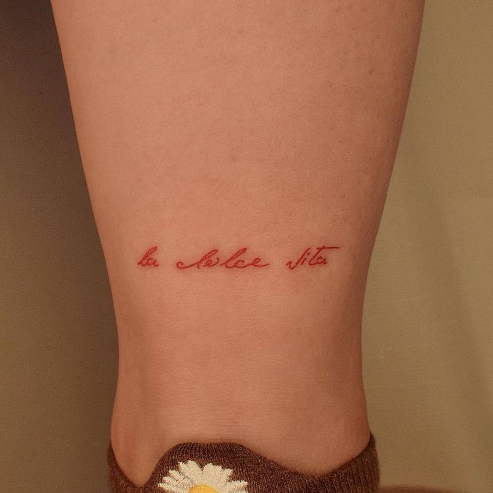 """La dolce vita"" lettering tattoo in red ink."