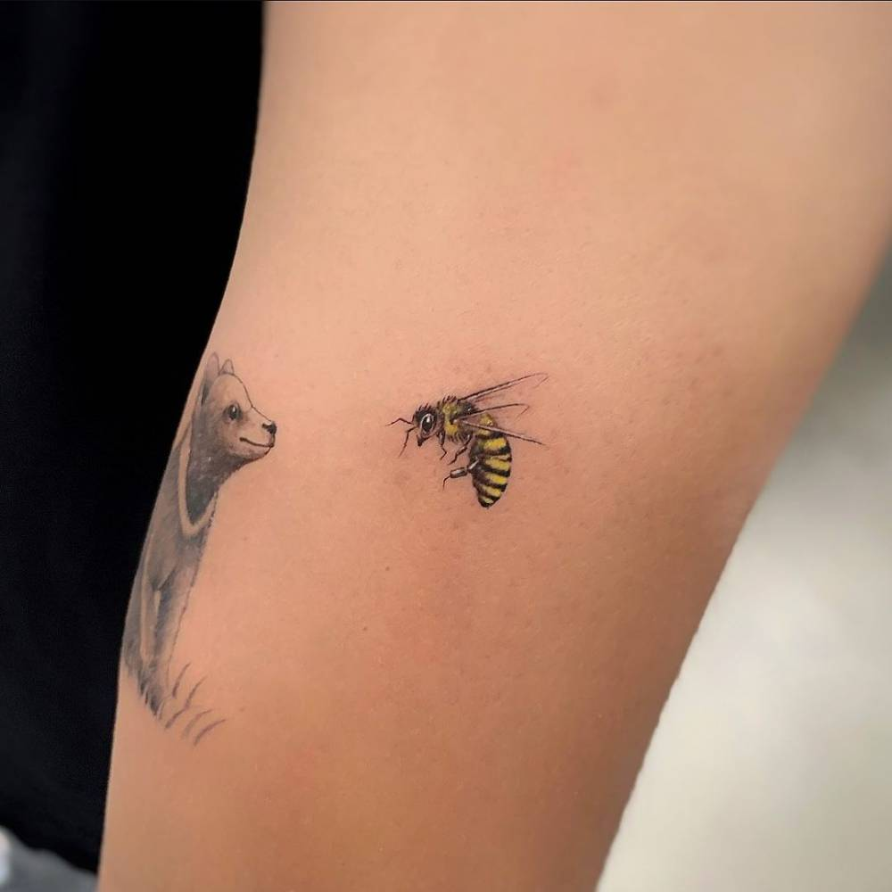 Micro-realistic bee tattoo on the upper arm.