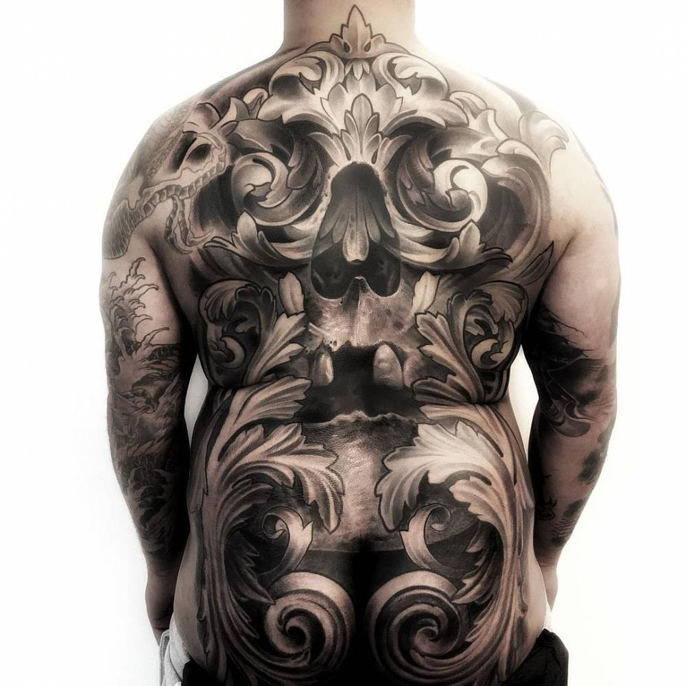 Black and grey skull and filigree backpiece tattoo.