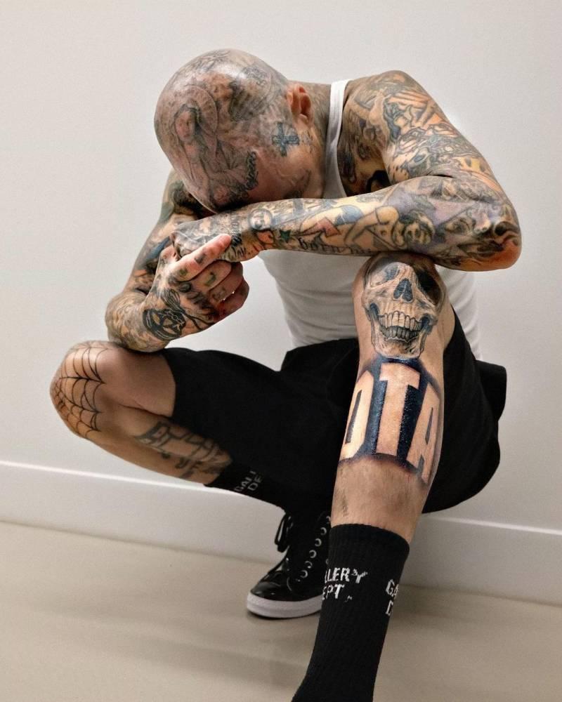 """DTA"" lettering tattoo on Travis Barker's shin."