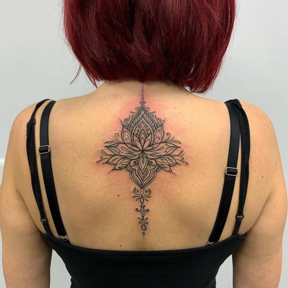 Ornamental lotus flower tattoo on the upper back.