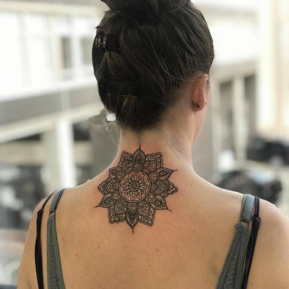 Mandala tattoo on the upper back.