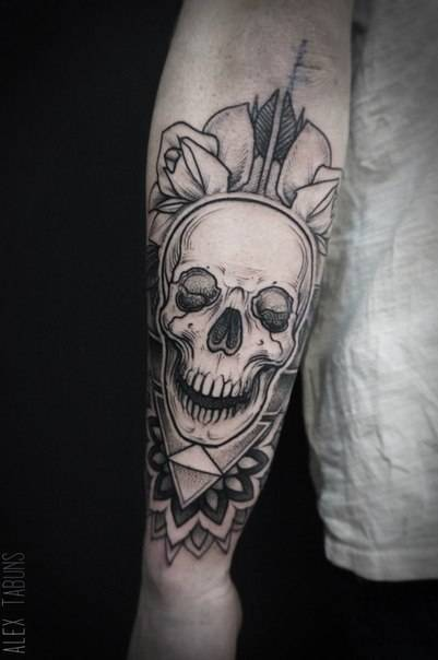 Blackwork skull tattoo on the forearm.