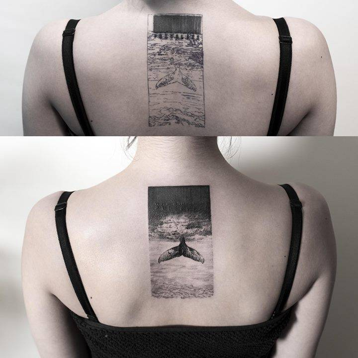 Whale tail cover-up tattoo on the upper back.