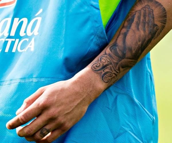 """Tatuajes de las manos que oran y de la palabra """"fé"""", situados en el antebrazo izquierdo de Neymar."""