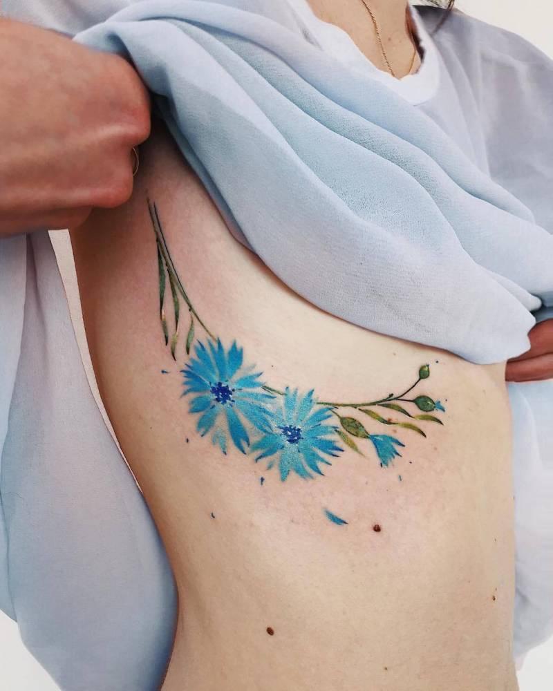 Watercolor style cornflower tattoo.