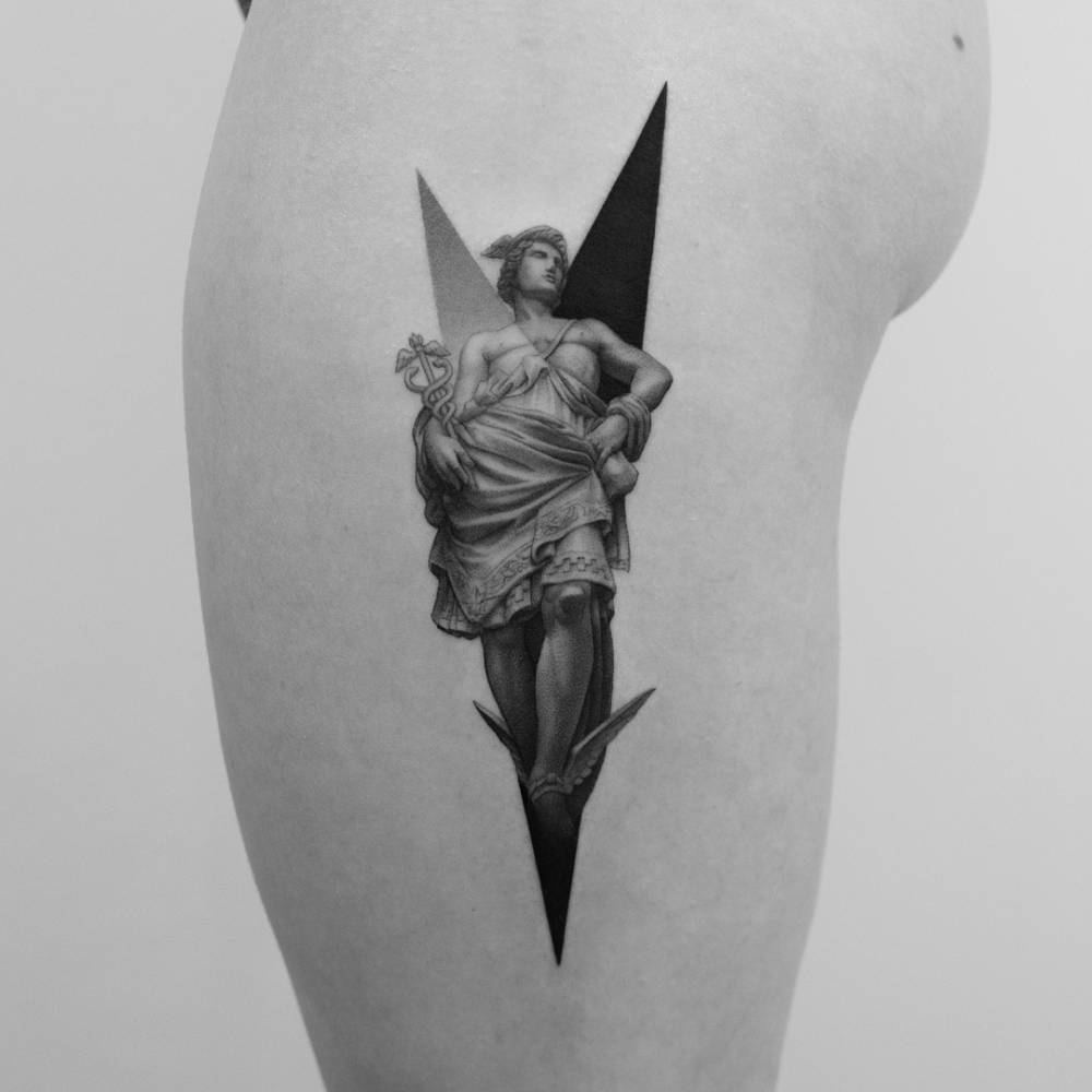 Hermes tattoo on the left thigh.