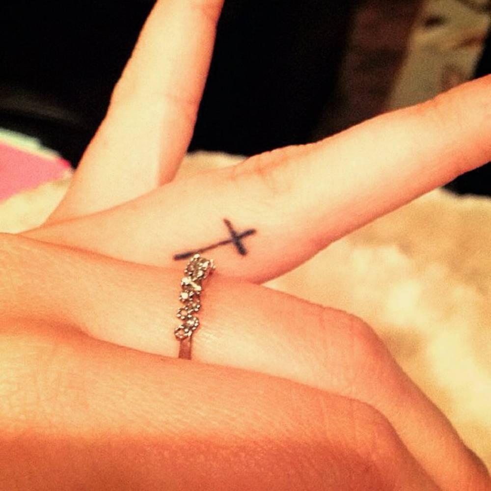 Finger Tattoo Of A Christian Cross On Harper Lee