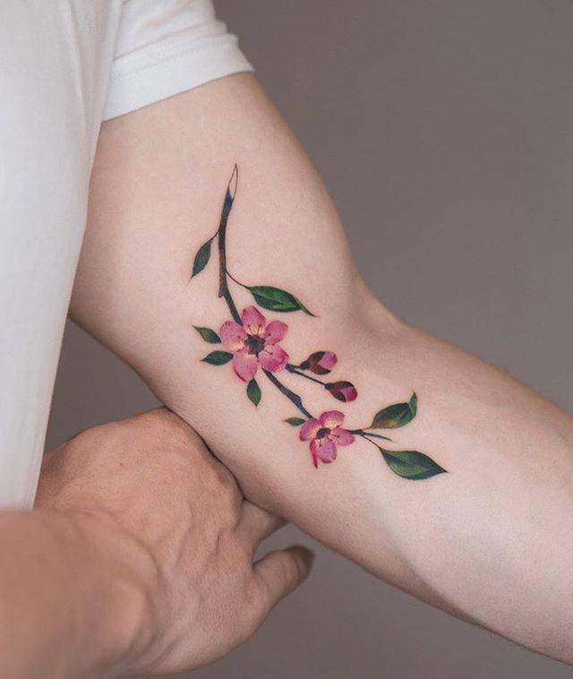 Watercolor plum blossom branch tattoo on the left arm.