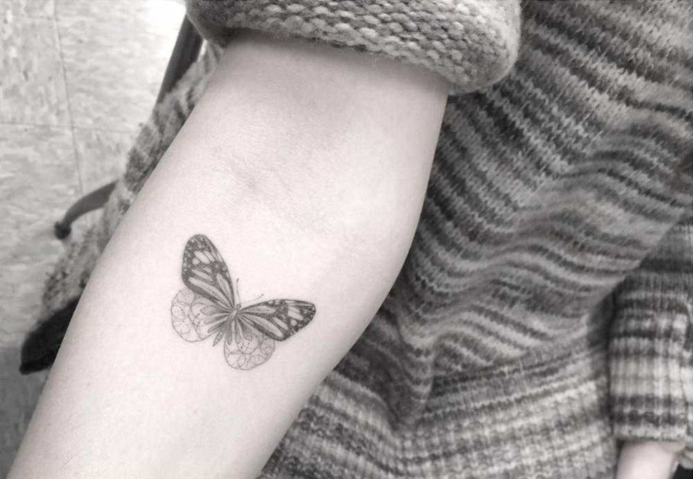 Fine line style butterfly tattoo on the right forearm.
