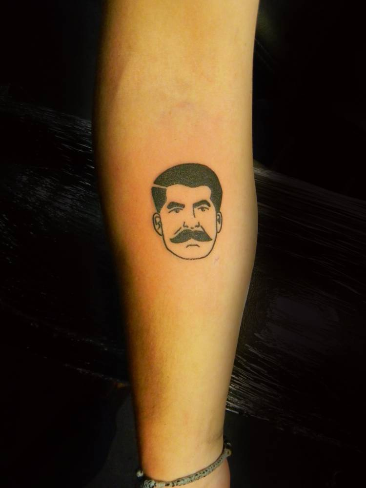 Small traditional style portrait tattoo on the right