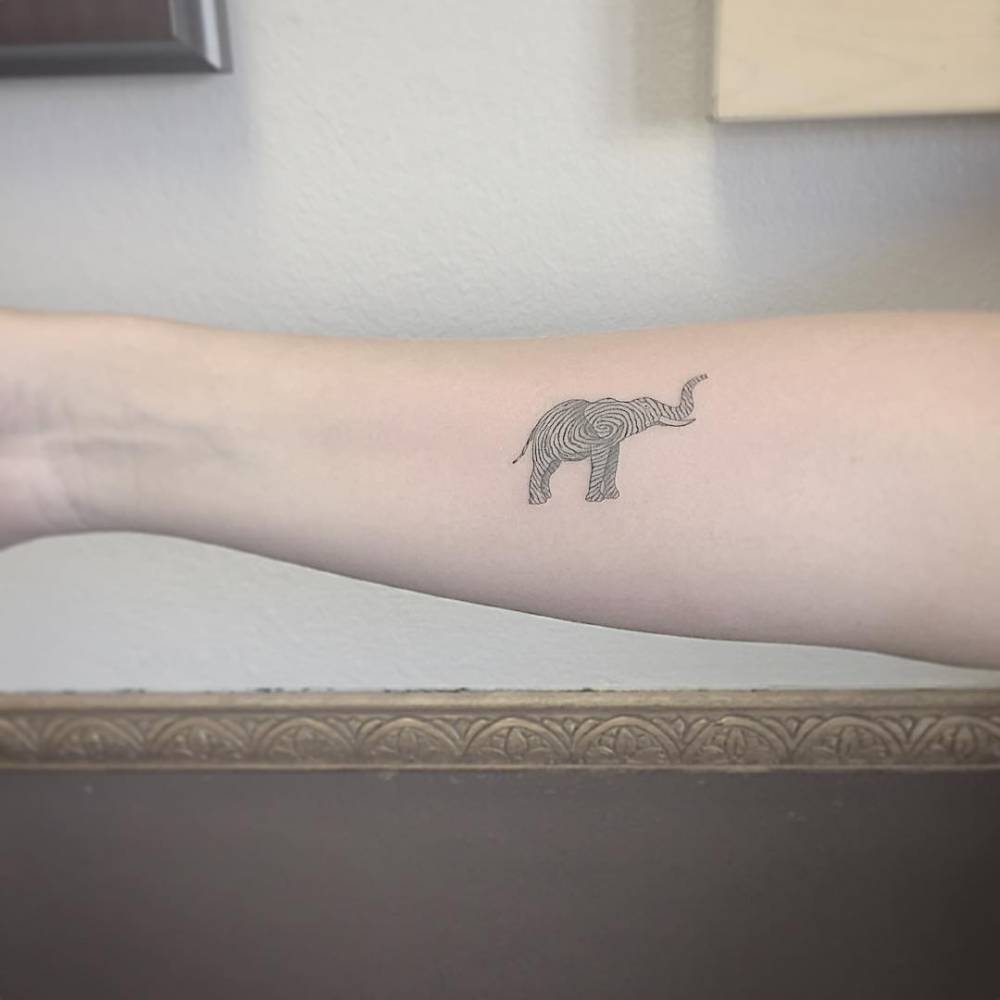 Small elephant-fingerprint tattoo on the right forearm.