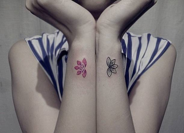 Matching lotus flower tattoos on the wrists.