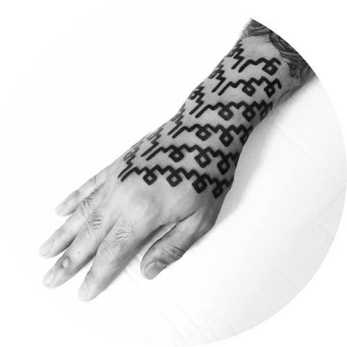 Custom pattern tattoo on the right forearm, wrist and hand.