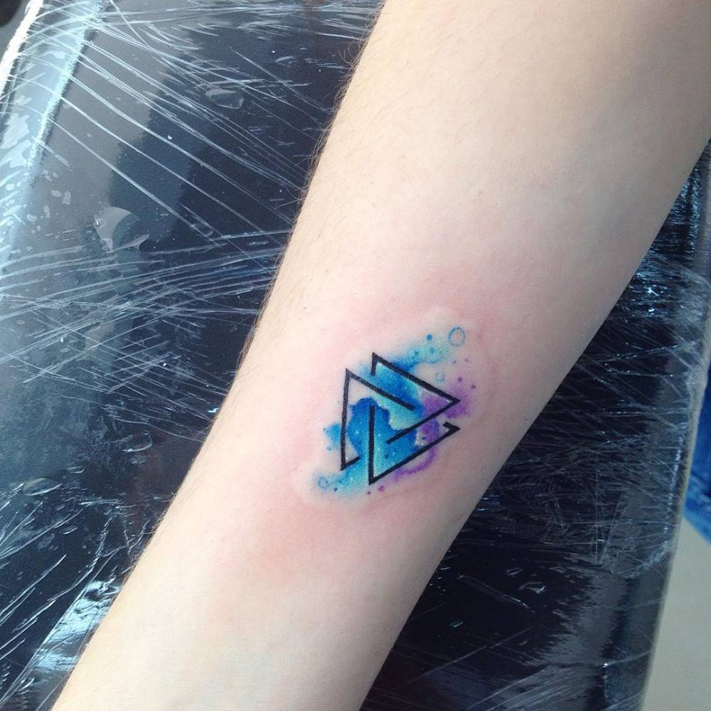 Watercolor style valknut as trefoil knot or triquetra on the right inner forearm.