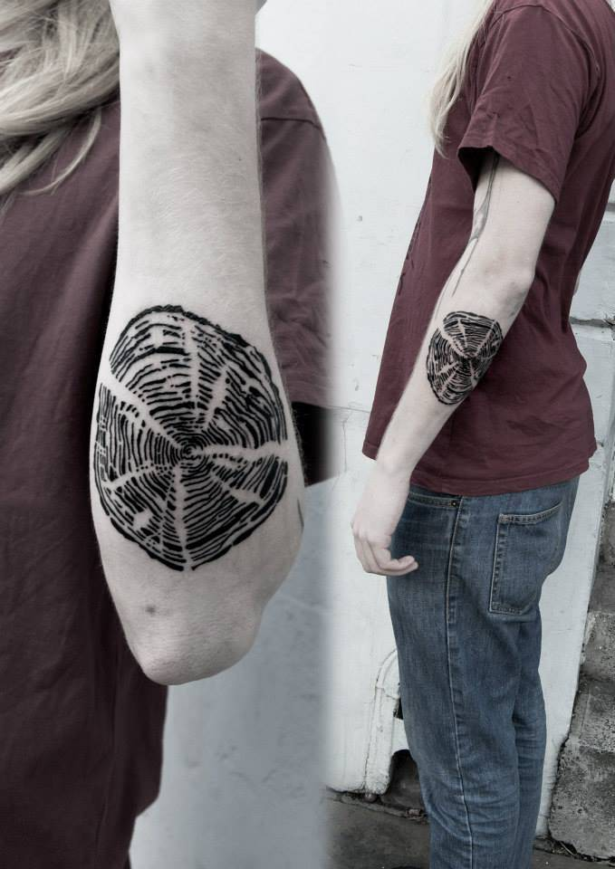 Tree-ring tattoo on the left forearm.