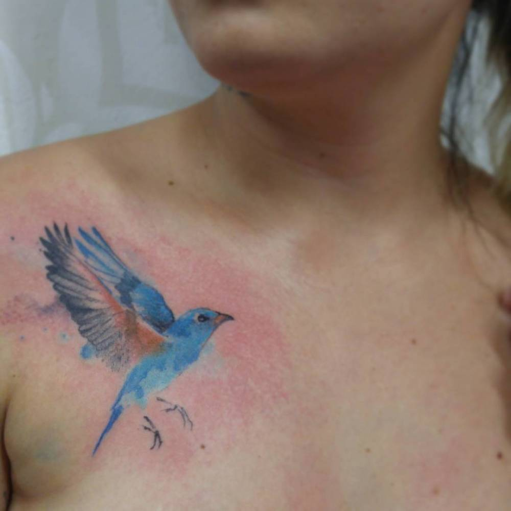 Watercolor style bluebird tattoo on the right side of