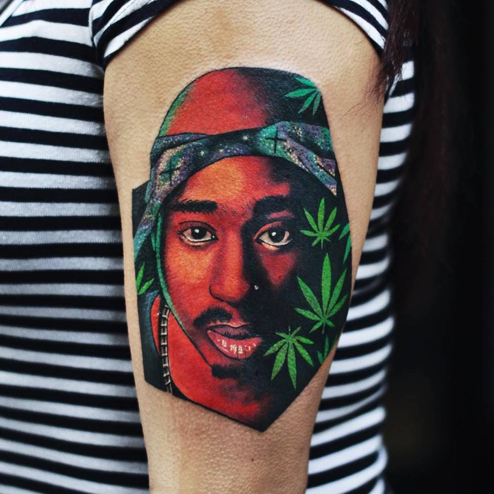 Psychedelic style Tupac portrait tattoo on the left upper arm.