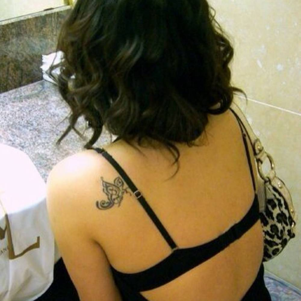 Shoulder blade tattoo of a blue butterfly by tattoo