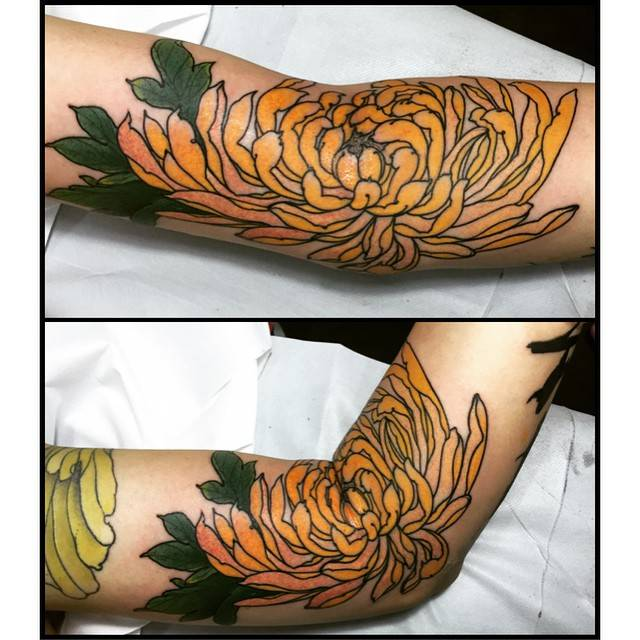Japanese style chrysanthemum tattoo on the left arm.