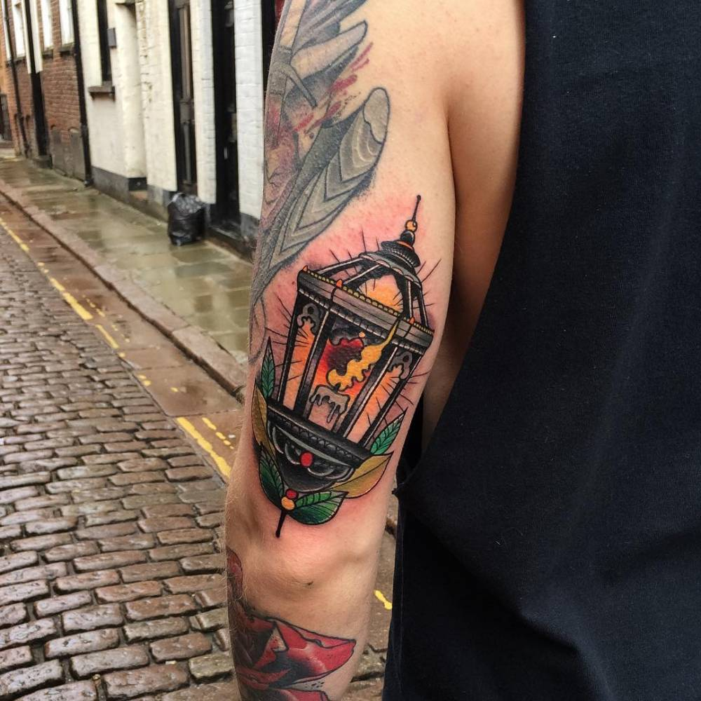Neotraditional lantern tattoo on the left tricep.