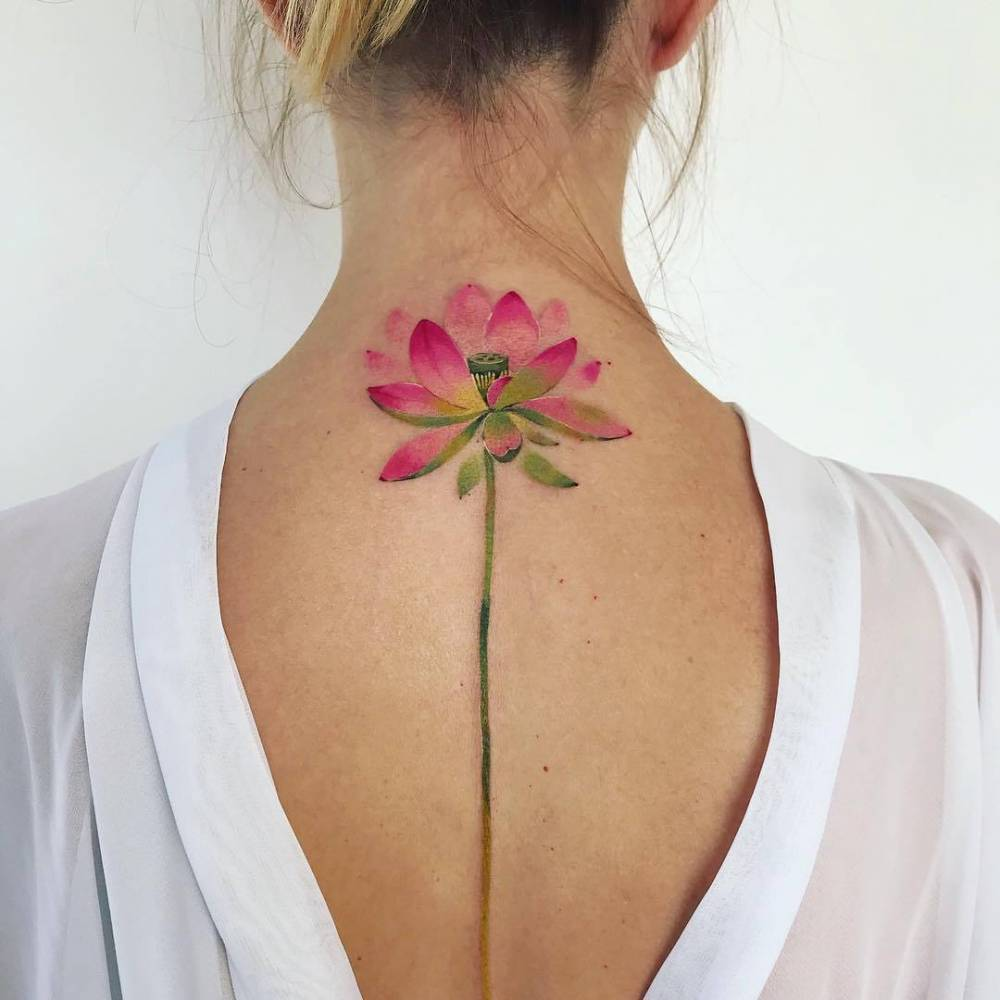 Watercolor lotus flower tattoo on the back.