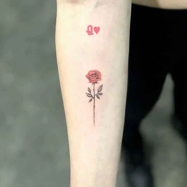 Red rose tattoo on the inner forearm.