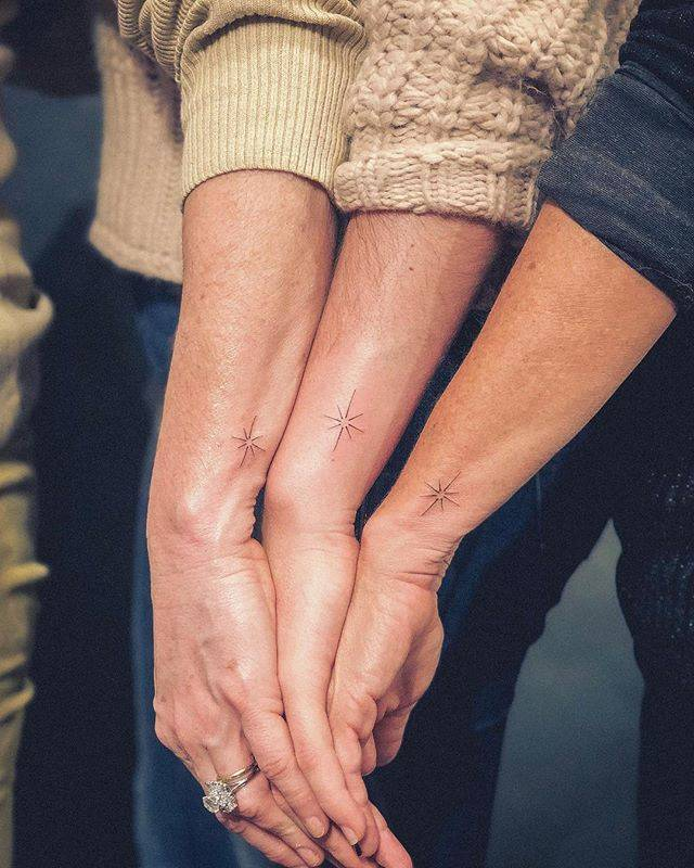 Matching star tattoos on the wrists.